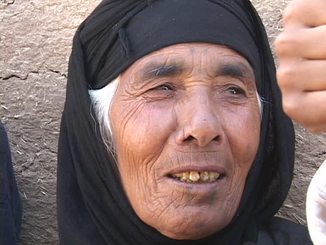 IRAQ - CIRCA 2003: A mature Muslim woman leans against a wall circa 2003 in rural Iraq.