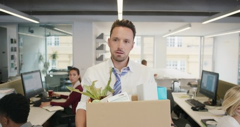 Businessman getting fired carrying box of personal belongings being made redundant in recession sad worried failure