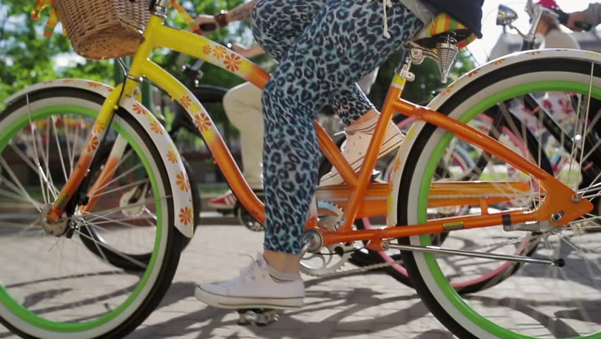 Woman feets and pedals of moving bicycle focus in among  another  people cycling