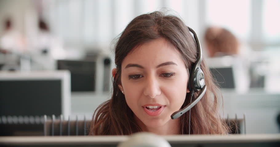 Young woman working in a call center using a headset