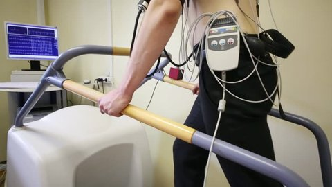 Young man walking on a treadmill during the making of electrocardiogram