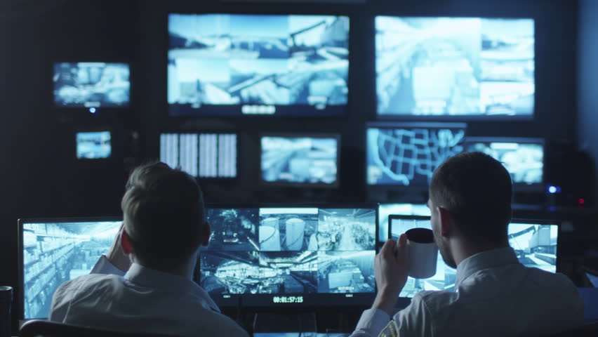 Two security officers noticed a trespasser on a surveillance computer screen in a dark monitoring room. Shot on RED Cinema Camera in 4K (UHD).