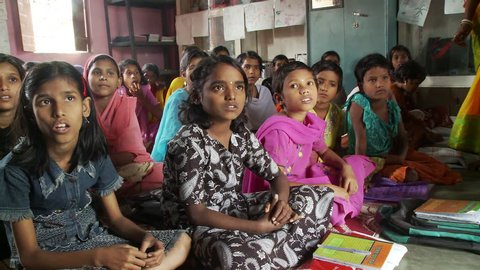 Baruipur, India - CIRCA 2013 - Girls in school sitting on mats and listening