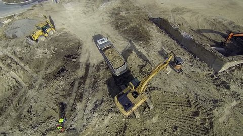 Aerial flight over earth moving machines and construction site. Construction crews prepare a site for a building . Digger, truck and bulldozer preparing ground for construction.