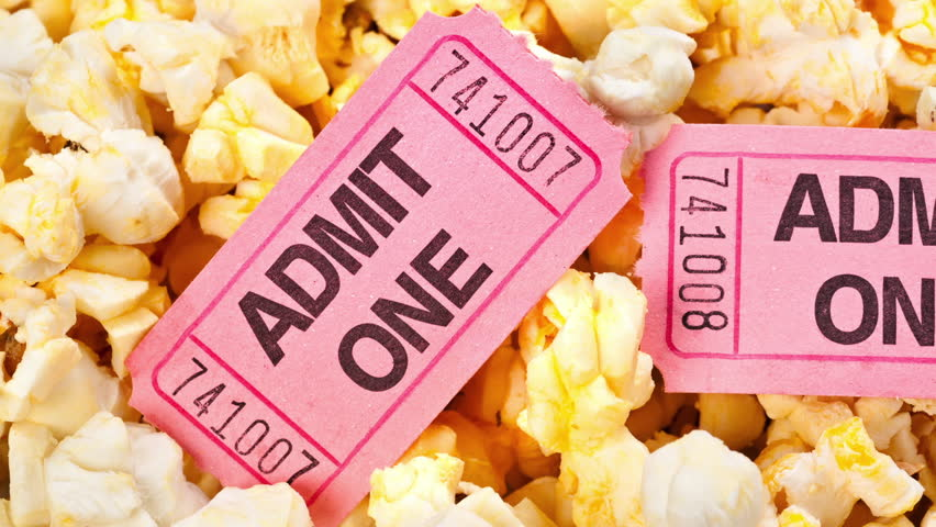 Motion over the top of a tub of fresh, hot popcorn with pink movie tickets for admission into the theater.