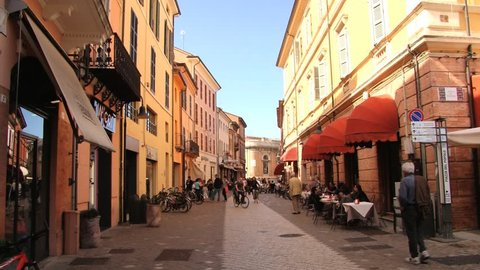 RAVENNA, ITALY – MAY, 12, 2013: Unidentified people ride bicycles by the pedestrian street in Ravenna, Italy.