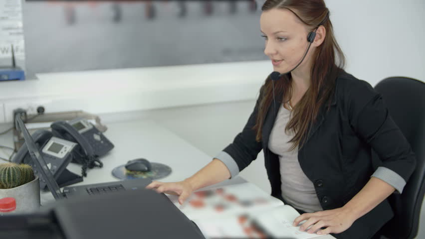 In this video, we can see an operator answering the phone and accepting her first client for today. She looks very friendly. | Shutterstock HD Video #14272421