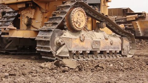 Bulldozer machine is leveling construction site. Earthmover with caterpillar is moving earth outdoors.