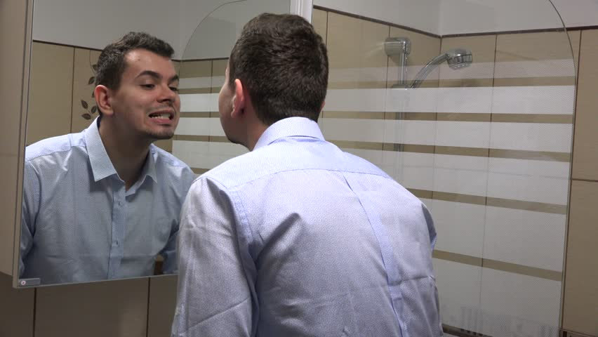 Young business person at home before work checking his teeth and using mouthwash