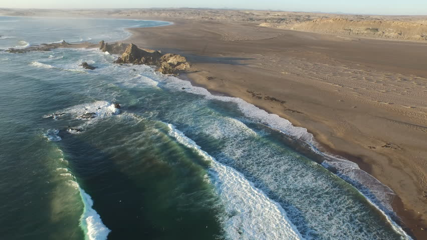 High angle aerial over beach and coastline to rocky outcrop, Namibia, 2015