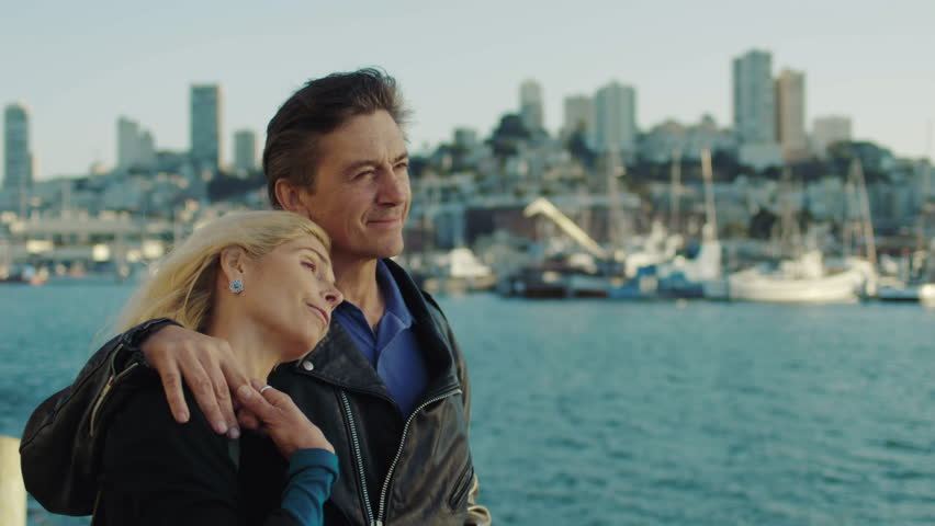 Middle-aged couple look at each other as they watch the sunset over the San Francisco Bay.