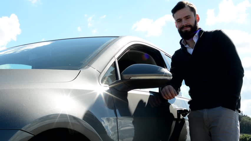 Young handsome hipster man stands beside the car and smiles to camera - countryside | Shutterstock HD Video #14348041