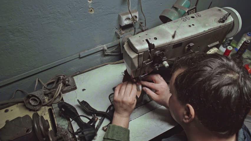 Shoemaker repairing shoes. Slow motion. Workshop