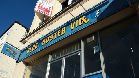 Pedestrians pass bankrupt Blockbuster video store. Newbury UK. Feb 2014