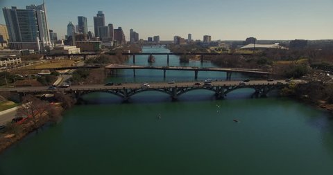 The camera flies over Lamar Boulevard and Lamar Pedestrian Bridge before reducing altitude and flying under a railroad bridge to reveal kayakers and paddle boarders on Lady Bird Lake in Austin, Texas.