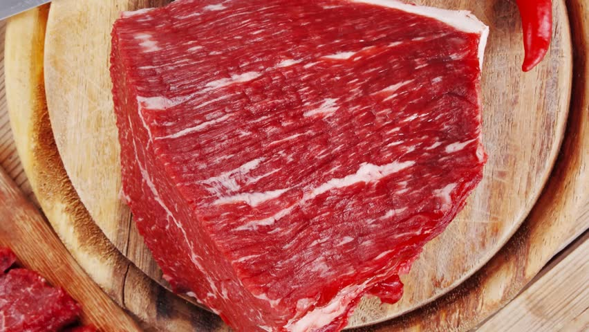 fresh raw beef meat steak and chunk with red hot pepper and dill on wooden cut plates over table 1920x1080 intro motion slow hidef hd
