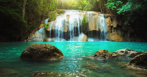 Idyllic waterfall and amazing nature. Sunlight and wild pond in jungle forest