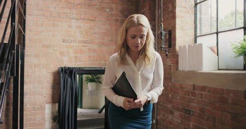 Business woman team leader walking through busy office meetings