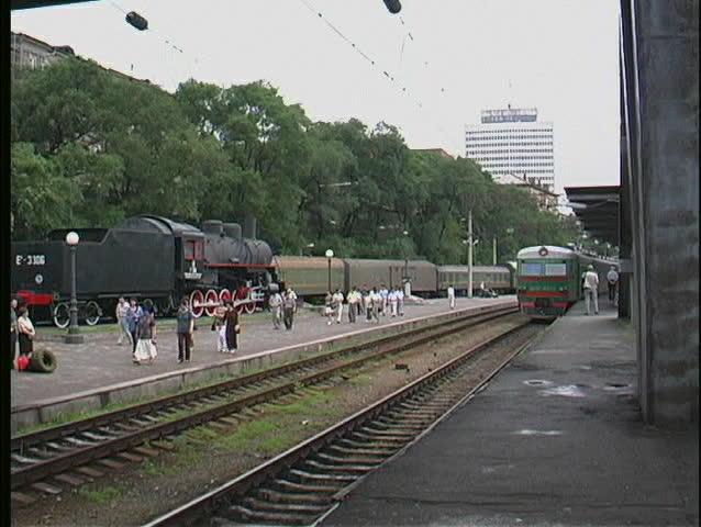 A green trans Siberian railway passenger train pulls into a Russian station.