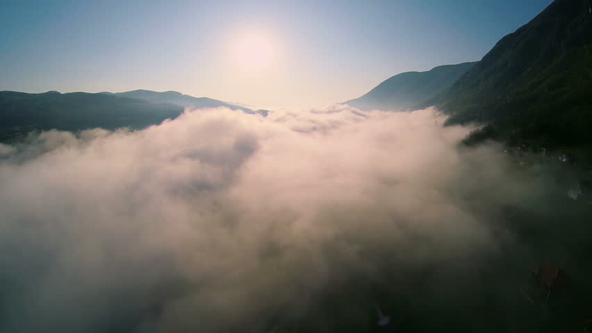 Above the clouds of mist between the mountains and hills at sunrise. Aerial Slow flying. Amazing scene of morning mist near the mountain peaks | Shutterstock HD Video #14428051