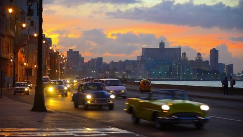 Cuba, Havana, Centro Habana, the Malecon, Vedado skyline at sunset, classic 1950's American cars