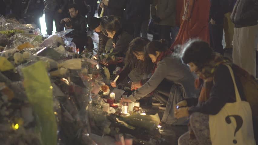 Paris terror attacks - Shrine at night, place de la République Shrine, flowers, and people paying tribute at night on place de la République after Paris terror attacks on November 13, 2015