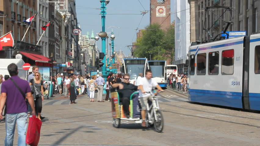 AMSTERDAM, HOLLAND - AUGUST 1: Tram drives along Dam square, with tourists crossing the street, on August 1, 2011 in Amsterdam, Holland. Amsterdam is a major travel destination for tourists.