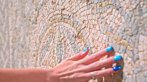 Fingers slide over mosaic picture. Female hand with colorful fingernails touch ancient mosaic wall in Carthage ruins in Tunisia.