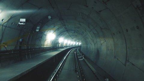 Train riding fast in a dark underground tunnel in the modern city