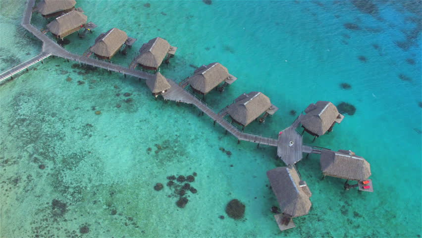 AERIAL: Flying above luxury secluded overwater beachfront villas with perfect exotic ocean view on beautiful tropical island with sandy coastline and palm trees, perfect for dreamy romantic honeymoon