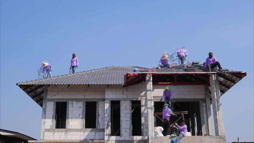 NAKHON RATCHASIMA -FEB 10 : unidentified construction workers installing roof tiles for home building on February 10, 2016 in Nakhon Ratchasima, Thailand