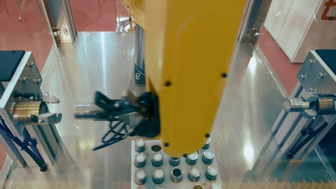 Industrial robot manipulator yellow color in the assembly shop is preparing items for later use on the automated line. Shot in motion