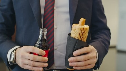 Close up of businessman eating hot dog and drinking coke from the bottle