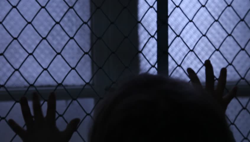 Helpless Child Shaking A Metal Fence Trying To Escape. Silhouette of children hands on the window fence. Refugees or abandoned child. Mental Institution. Family violence. Fingers on the fence