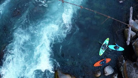 Aerial shot above a group of kayakers preparing to paddle down rapids in water of deep blue river in summer in Patagonia Chile - 2K HD