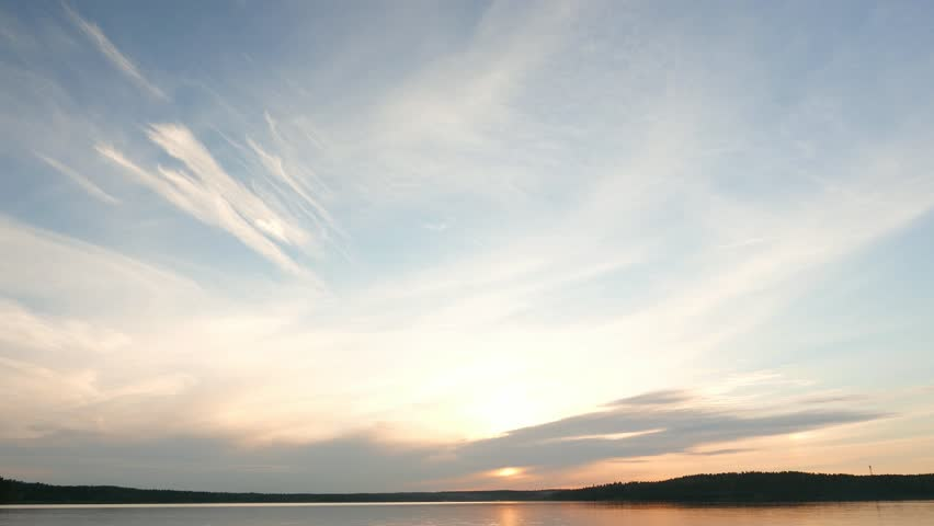 Light stretched clouds over evening sky, lake sunset skies time lapse shot. Sun disk ahead, hide behind dense stripe of clouds, move down to horizon line. Reflex on flat water #14637331
