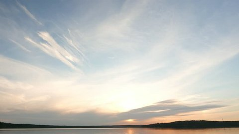 Light stretched clouds over evening sky, lake sunset skies time lapse shot. Sun disk ahead, hide behind dense stripe of clouds, move down to horizon line. Reflex on flat water