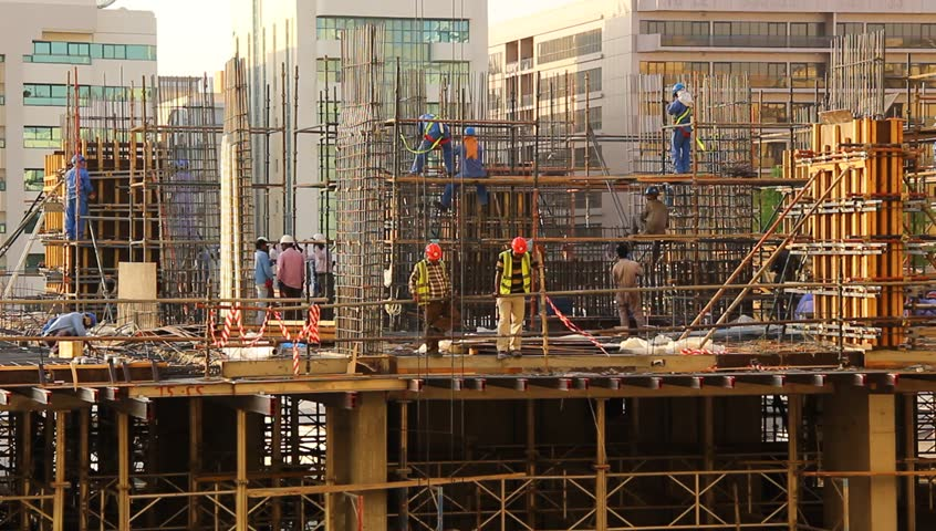 DUBAI, UNITED ARAB EMIRATES - OCTOBER 26, 2013: Construction site bustle, unidentified workers at rebar frame, long time lapse. Expatriate builders works at building project, erect and prepare carcase