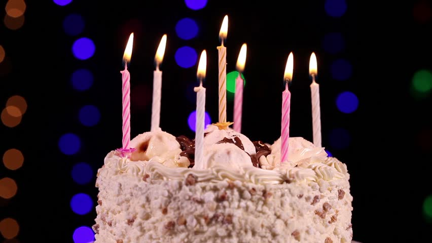 Happy Birthday Cake With Burning Candles In Front Of Black Background Close Up