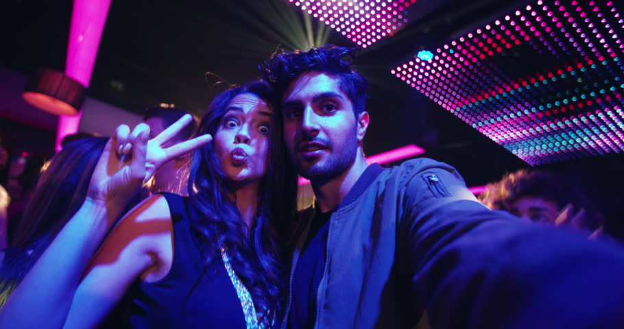 Fashionable friends at nightclub taking selfies and pulling faces for the photo with people, music and disco lights in the background of the party in the night club #14730751