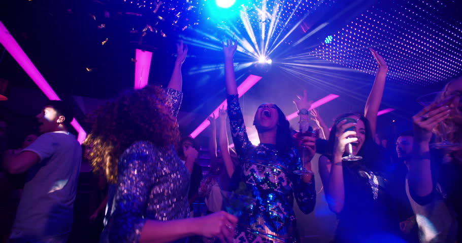 African-American woman dancing at party with cocktail in her hand, laughing at her girl friends on the dance floor at a modern disco nightclub. Group is cheering as confetti is flying in slow motion
