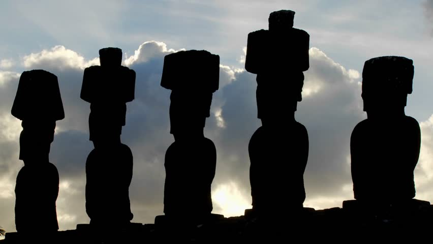 Clouds move mysteriously behind Easter Island statues.
