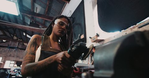 Low angle shot of a skilled afro-american woman craftsperson with dreadlocks and tattoos using a grinder on a piece of metal with sparks