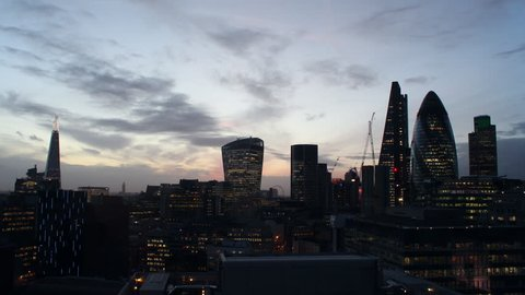 Time lapse video of the City of London financial district dusk to night. The Shard, Walk-ie Talkie, Cheese Grater, and Gherkin buildings illuminated at night. Traffic and London Eye in background.