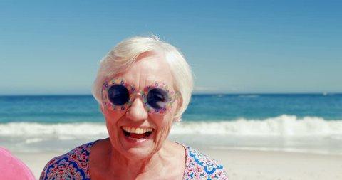 Portrait of senior Caucasians friends with funny sunglasses having fun at the beach