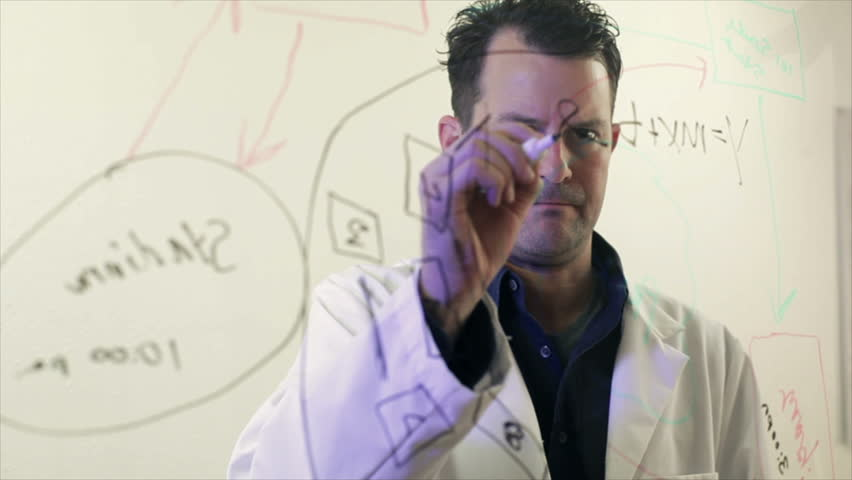 A scientist or chemist writes out a formula on a large transparent board.