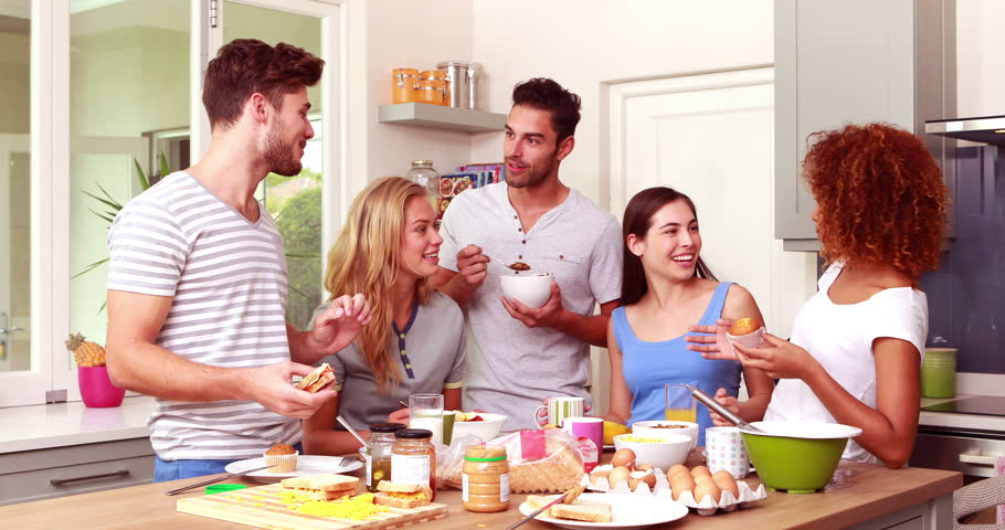 Friends Talking While Eating Breakfast Together At Home