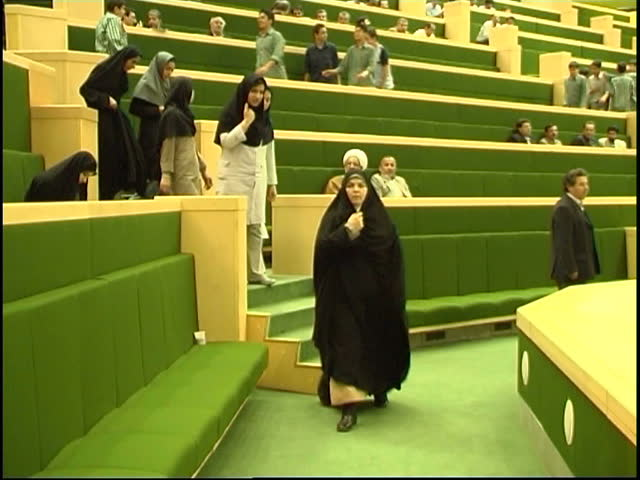 Parliament, Tehran, Iran - 2005 - Iranian politician and MP, Mrs. Rafat Bayat walks past a group of young girls sitting in the public gallery.