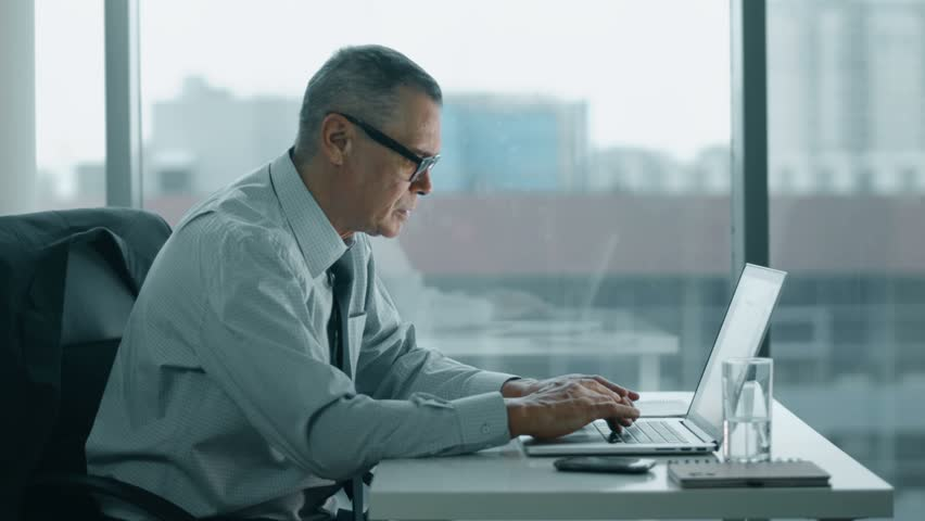 Elderly businessman working with computer in modern office. his back is hurts | Shutterstock HD Video #14813101