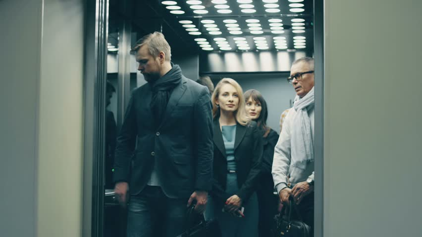 Business people call an elevator, get in when it arrives | Shutterstock HD Video #14813284